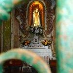 La Madonnina della cappella dell'Acquasanta risplende attraverso le inferriate